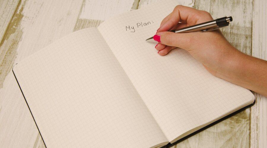 En hand som skriver i en bok